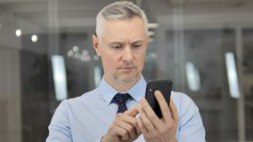 Grey Hair Businessman Using Smartphone, mensaje que mecanograf?a almacen de metraje de vídeo