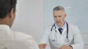 Grey Hair Doctor Telling Patient sobre a norma sanitária e o plano do tratamento video estoque