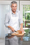 Grey hair man cutting bread in apron Royalty Free Stock Image