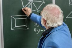 Grey hair professor drawing with piece of chalk. At blackboard royalty free stock image