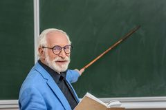 Grey hair professor holding book and pointing on something. At blackboard royalty free stock image