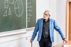 Grey hair professor looking. At blackboard royalty free stock photos