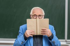 Grey hair professor looking out. From book stock photography