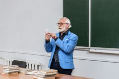 Grey hair professor looking at smartphone. In lecture room royalty free stock image