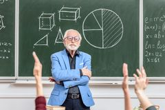 Grey hair professor looking at students. Rising hands royalty free stock photos