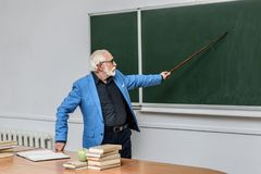 Grey hair professor pointing on something. At blackboard stock photography