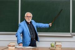 Grey hair professor pointing on something. At blackboard stock image
