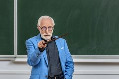 Grey hair professor pointing on something. At lecture hall royalty free stock photos