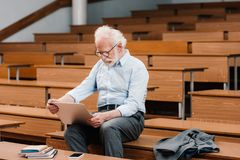 Grey hair professor sitting on desk in empty lecture room. And using laptop royalty free stock images