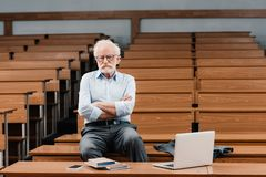 Grey hair professor sitting in empty lecture room. With crossed arms royalty free stock photos