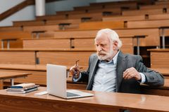 Grey hair professor sitting in empty lecture room and looking. At laptop royalty free stock images