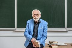 Grey hair professor sitting on table in lecture room. And holding book stock photography