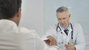 Grey Hair Senior Doctor Giving recept till patienten, når att ha diskuterat resultat arkivfilmer