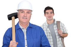 Grey-haired builder with apprentice Royalty Free Stock Photo
