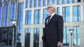 Grey-haired company director standing outdoors, confident businessman waiting stock images