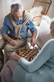 Grey haired couple playing chess at home Stock Images