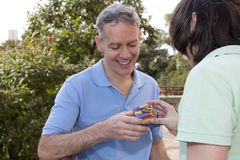 Grey haired dad and teenager son. Father Day. Young man is giving a present to parent in wooded area. Concept of family, relation. Grey haired dad and teenager royalty free stock photos