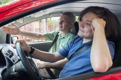 Grey haired dad is trying to teach son how to drive. Complain. Concept of family, paternity. Grey haired dad is trying to teach teenage son how to drive royalty free stock images