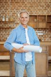 Grey-haired engineer posing with a blueprint. Happy smile. Upbeat senior engineer standing in a studio apartment, holding a blueprint rolled in tube and smiling Stock Photos