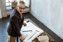 Grey-haired experienced interior designer standing near sketches royalty free stock image