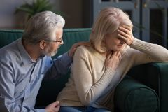 Grey haired husband supporting unhappy mature woman wife at home stock image