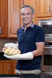 Grey haired man holding apple pie. A handsome man with grey hair holding a pie he baked and pulled out of the oven Royalty Free Stock Photography