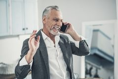 Grey-haired man laughing out loud after hearing good news royalty free stock photography