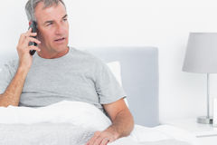 Grey haired man making a phone call in bed Stock Images