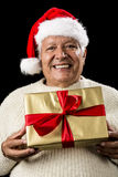 Grey-Haired Man Offering Golden Wrapped Present. Cheerful aged gentleman offering a golden wrapped gift, which he is holding in front of his chest with both Stock Photography