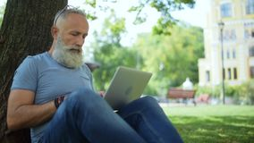 Grey haired man sitting under tree and typing stock footage