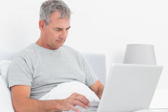Grey haired man using his laptop in bed Royalty Free Stock Photos