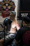 Grey hair man sitting topless on a chair is having his left arm tattooed by New Choice Tattoo  stock photography