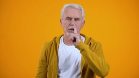 Grey-haired pensioner showing silence gesture against orange background, secret. Stock footage stock video