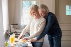 Loving attractive mature couple preparing breakfast together stock photos