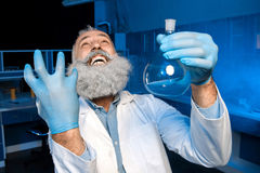Grey haired scientist celebrating success of scientific experiment and holding flask with reagent. Happy grey haired scientist celebrating success of scientific Royalty Free Stock Photo