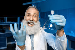 Grey haired scientist celebrating success of scientific experiment and holding flask with reagent. Happy grey haired scientist celebrating success of scientific Stock Images