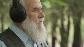 Grey-haired senior man listens music in headphones stock video