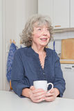Grey haired woman with mug Stock Photography