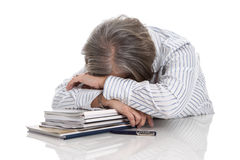 Grey haired woman sleeping on books - overworked isolated on whi. Te background - burn out Royalty Free Stock Image