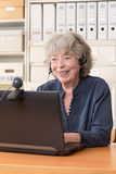 Grey haired woman video chat. Grey haired woman sitting in front of her computer having a video chat, copyspace Stock Photos
