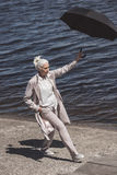 Grey haired woman walking with umbrella on river shore at daytime. Casual grey haired woman walking with umbrella on river shore at daytime Royalty Free Stock Images