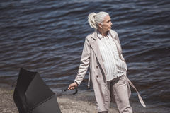 Grey haired woman walking with umbrella on river shore at daytime. Casual grey haired woman walking with umbrella on river shore at daytime Stock Image