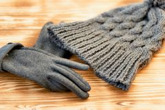 Grey hat and gloves knit on a wooden surface.The concept is to keep warm in autumn or winter day. Grey hat and gloves knit on a wooden surface. The concept is to royalty free stock photo