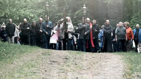 Grey head and beard old man carry cross like Jesus Christ. people procession. VILNIUS, LITHUANIA - JUNE 02, 2017: Old grey head and beard senior man carrying stock video