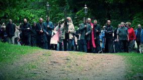 Grey head and beard senior man carry cross like Jesus Christ. People procession. VILNIUS, LITHUANIA - JUNE 02, 2017: Old grey head and beard senior man carrying stock footage