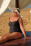 Grey-headed senior woman relaxing on the beach. Elegant hat and royalty free stock photography