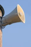 Grey horn loudspeaker on the pole over blue sky Stock Photos