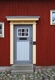 The grey house door in the old red wall Royalty Free Stock Photo