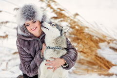 Grey husky dog licks girl in winter background yellow reeds Stock Images
