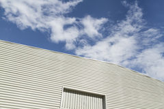 Grey industrial building against a cloudy sky Royalty Free Stock Photography